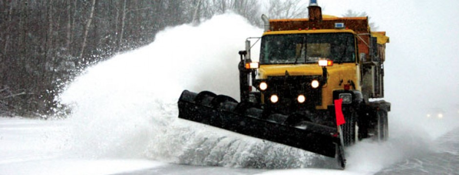 Passing snowplow with snow spraying off the plow blade